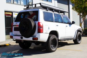 Rear left view of a Nissan GU Patrol Wagon in White On The Hoist @ Superior Engineering Deception Bay Showroom