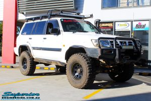 Right front side view of a White Nissan GU Patrol Wagon being fitted with Superior Hybrid 5 Link Radius Arms, 55mm Shock Tower Lift Kit & Bump Stop Extensions