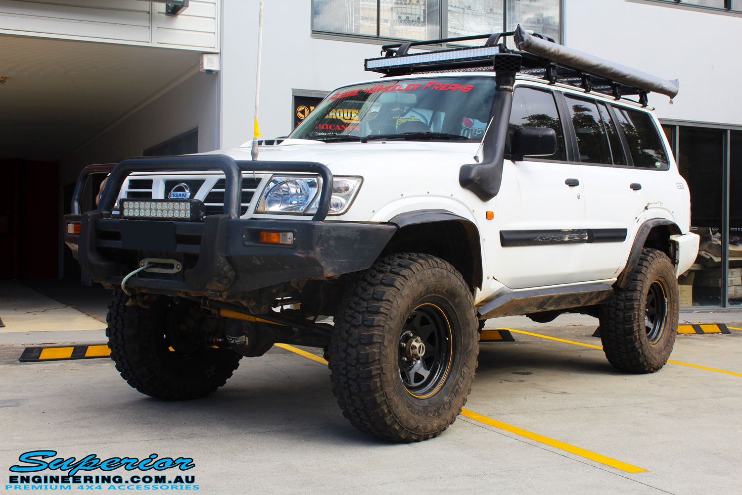 Left front side view of a White Nissan GU Patrol Wagon after being fitted with Superior Hybrid 5 Link Radius Arms, 55mm Shock Tower Lift Kit & Bump Stop Extensions