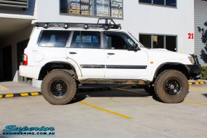 Right side view of a White Nissan GU Patrol Wagon being fitted with Superior Hybrid 5 Link Radius Arms, 55mm Shock Tower Lift Kit & Bump Stop Extensions