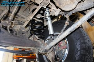 Rear left underbody shot of the fitted Fox 2.0 Performance Series IFP Rear Shock + Coil Spring