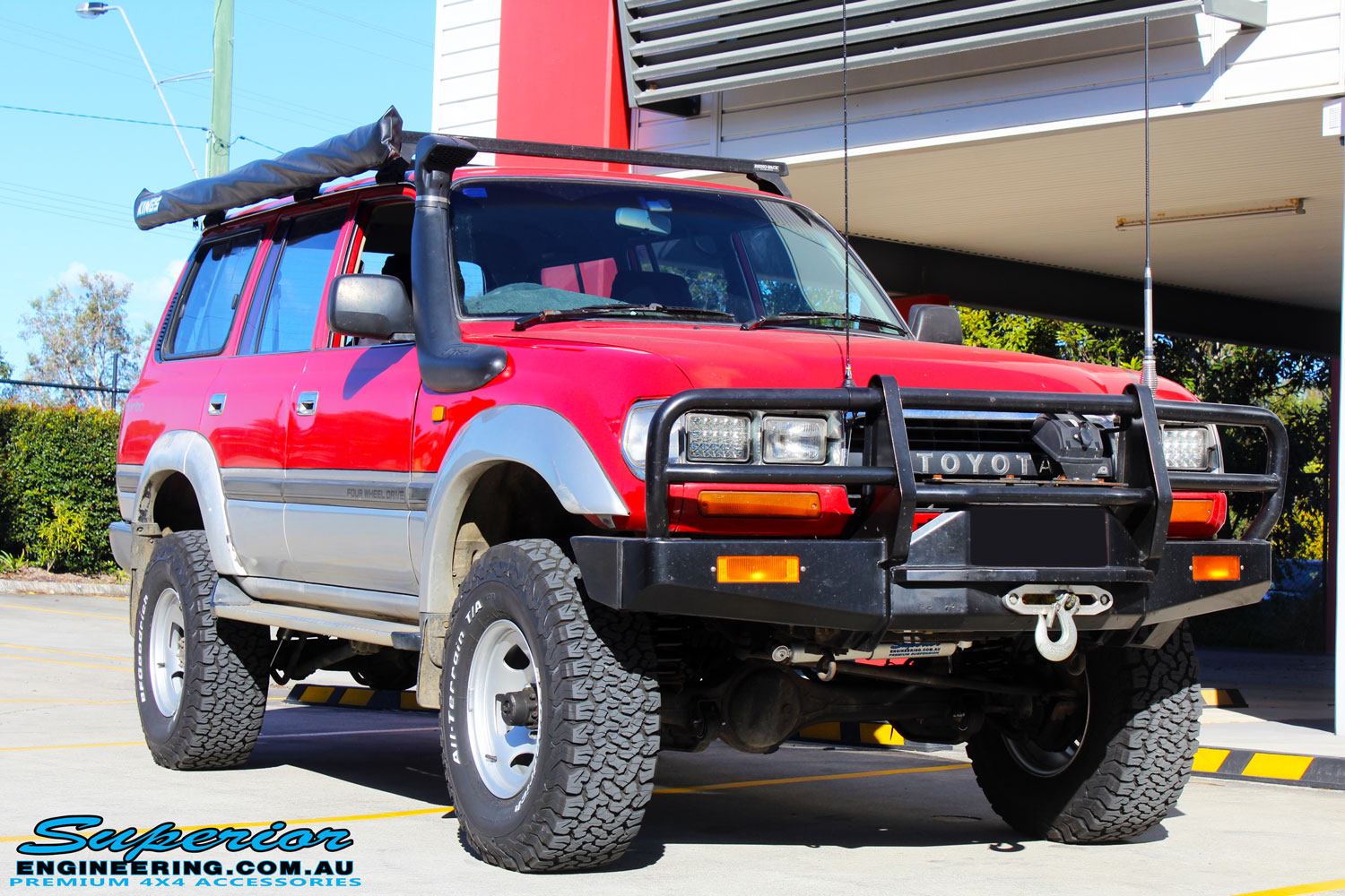 "Right front side view of a Red Toyota 80 Series Landcruiser after fitment of a Fox 2.0 Performance Series IFP 2"" Inch Lift Kit"
