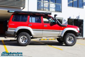 """Right side view of a Red Toyota 80 Series Landcruiser after fitment of a Fox 2.0 Performance Series IFP 2"""" Inch Lift Kit"""