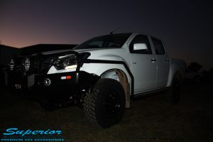 """Right front side view of a White Isuzu D-Max Dual Cab being fitted with a Superior Remote Reservoir 2"""" Inch Lift Kit, Airbag Man Leaf Air Kit, Ironman 4x4 Bullbar + Side Steps, VRS Winch, Safari Snorkel + King Wheels & Nitto Tyres"""