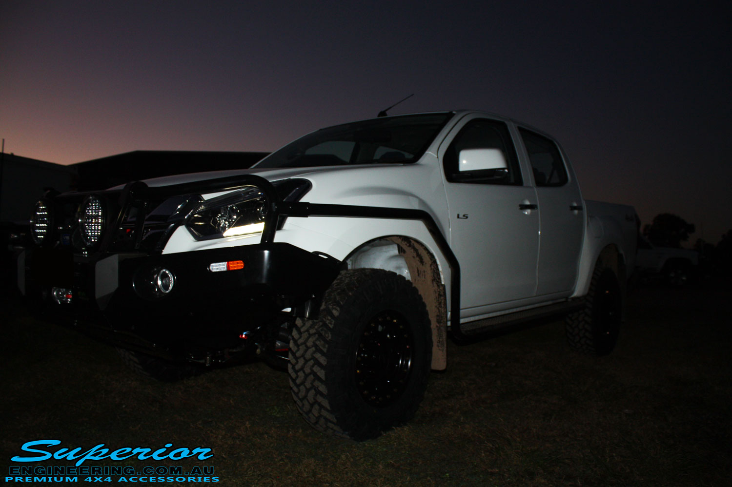 "Right front side view of a White Isuzu D-Max Dual Cab being fitted with a Superior Remote Reservoir 2"" Inch Lift Kit, Airbag Man Leaf Air Kit, Ironman 4x4 Bullbar + Side Steps, VRS Winch, Safari Snorkel + King Wheels & Nitto Tyres"