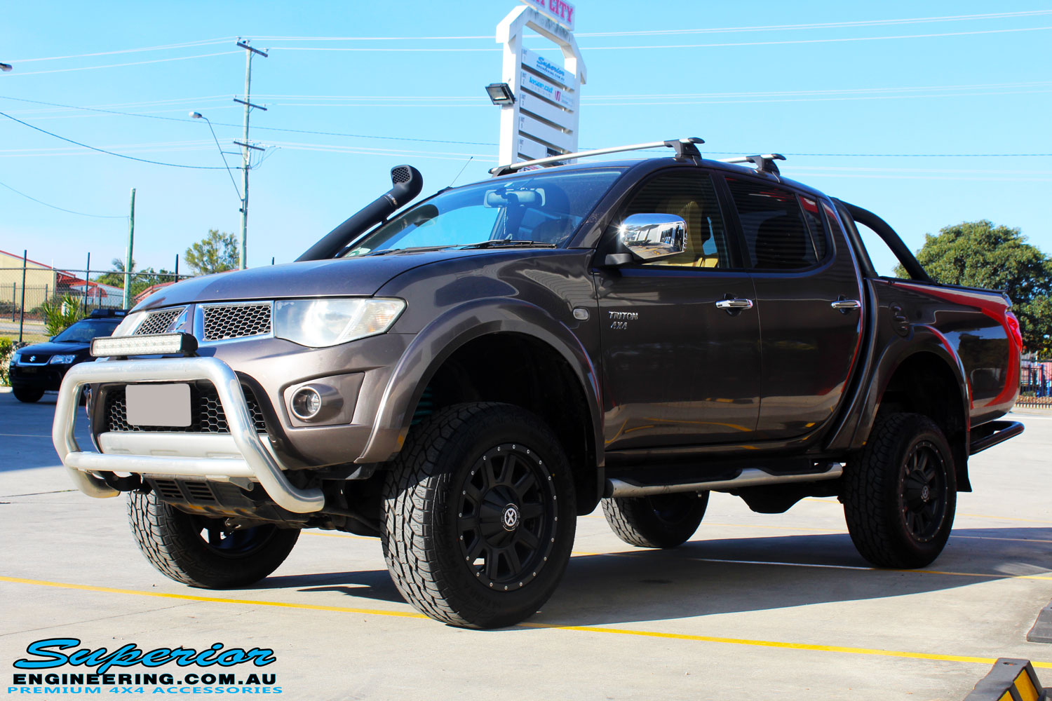 "Left front side view of a Mitsubishi MN Triton in Bronze after fitment of a Superior Nitro Gas 2"" Inch Lift Kit + 2"" Inch Body Lift"