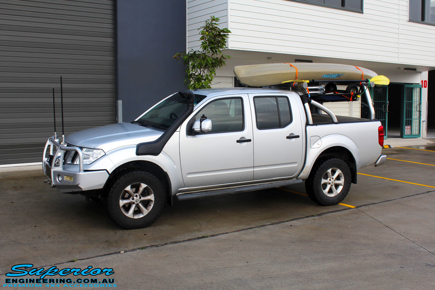 Left front side view of a Nissan D40 Navara in Silver On The Hoist @ Superior being fitted with a Chassis Brace/Repair Plate