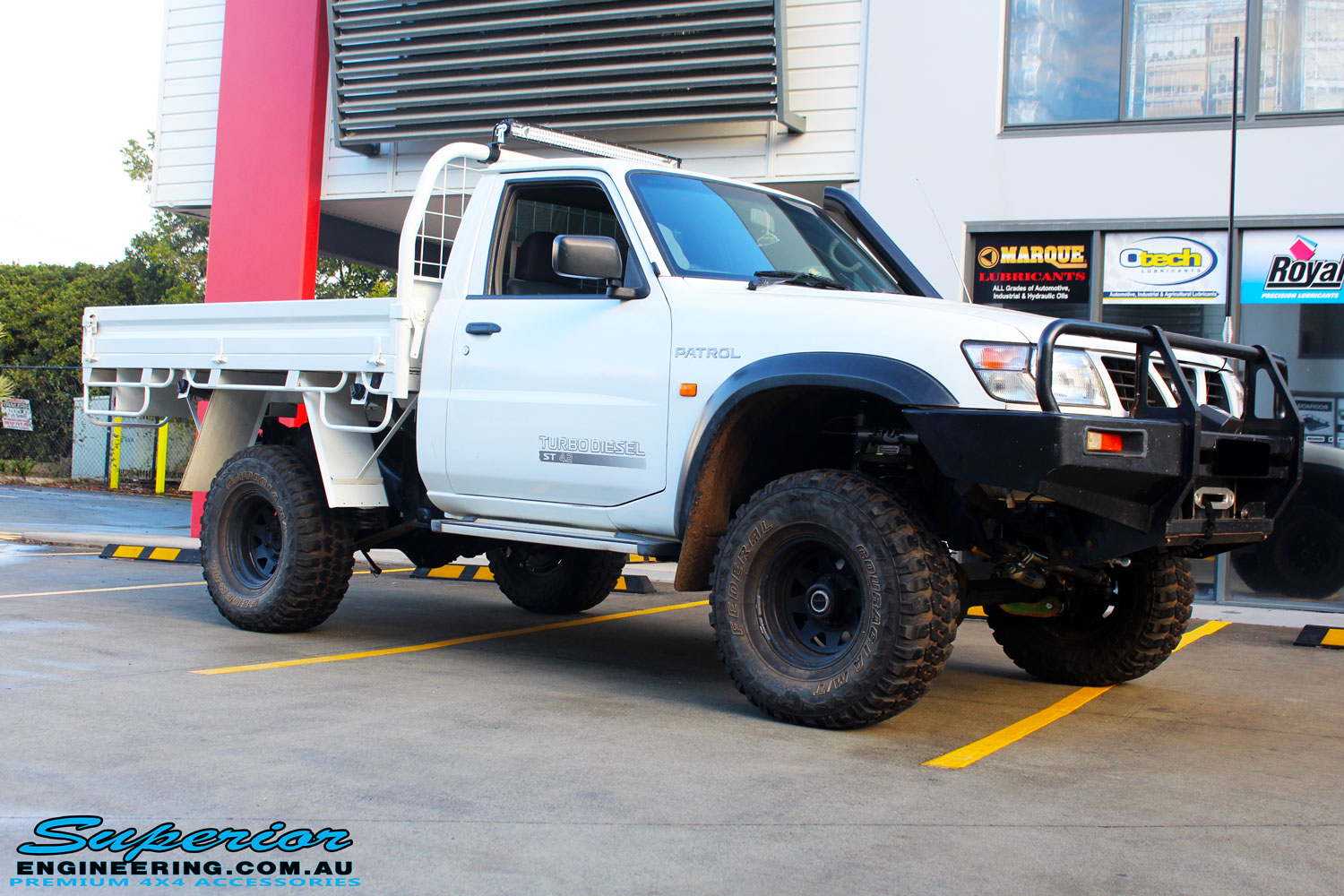 """Front right side view of a White Nissan GU Patrol Ute after fitment of the Superior 4"""" Inch Remote Reservoir Hyperflex Kit with Fox Shocks"""