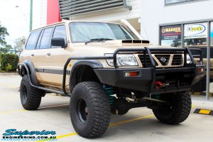 "Right front side view of a Gold Nissan GU Patrol Wagon being fitted with Superior Lower Control Arms, Adjustable Upper Control Arms, Comp Spec 4340m Drag Link, 4"" Inch Front & Rear Dobinson Coil Springs, Superior Coil Tower Brace and Superior 5"" Inch Remote Reservoir Front & Rear Shocks"