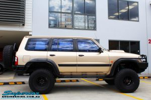 """Right side view of a Gold Nissan GU Patrol Wagon being fitted with Superior Lower Control Arms, Adjustable Upper Control Arms, Comp Spec 4340m Drag Link, 4"""" Inch Front & Rear Dobinson Coil Springs, Superior Coil Tower Brace and Superior 5"""" Inch Remote Reservoir Front & Rear Shocks"""