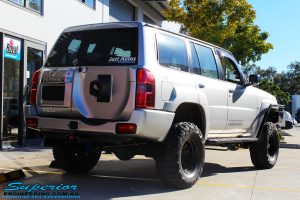 Rear right side view of a Grey Nissan Patrol GU Wagon after fitting a Superior Remote Reservoir Hybrid Dropped Radius 4 Inch Lift Kit with Hyperflex Radius Arms, Lower Control Arms, Tie Rod, Heim Draglink, Superior Front & Rear Sway Bar Kits, Rear Bumpstop and Superior Shock Tower Lift Kit