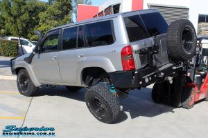 """Rear left side view of a rear right flexed Silver Nissan Patrol GU Wagon after fitting the Superior Remote Reservoir 4"""" Inch Hybrid Superflex Lift Kit with Fox Shocks"""