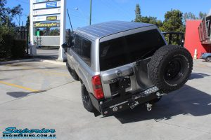 """Rear left view of a front right flexed Silver Nissan Patrol GU Wagon after fitting the Superior Remote Reservoir 4"""" Inch Hybrid Superflex Lift Kit with Fox Shocks"""