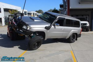 """Front left view of a front right flexed Silver Nissan Patrol GU Wagon after fitting the Superior Remote Reservoir 4"""" Inch Hybrid Superflex Lift Kit with Fox Shocks"""