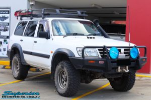 Right front side view of a Nissan GU Patrol Wagon in White On The Hoist @ Superior Engineering Deception Bay Showroom