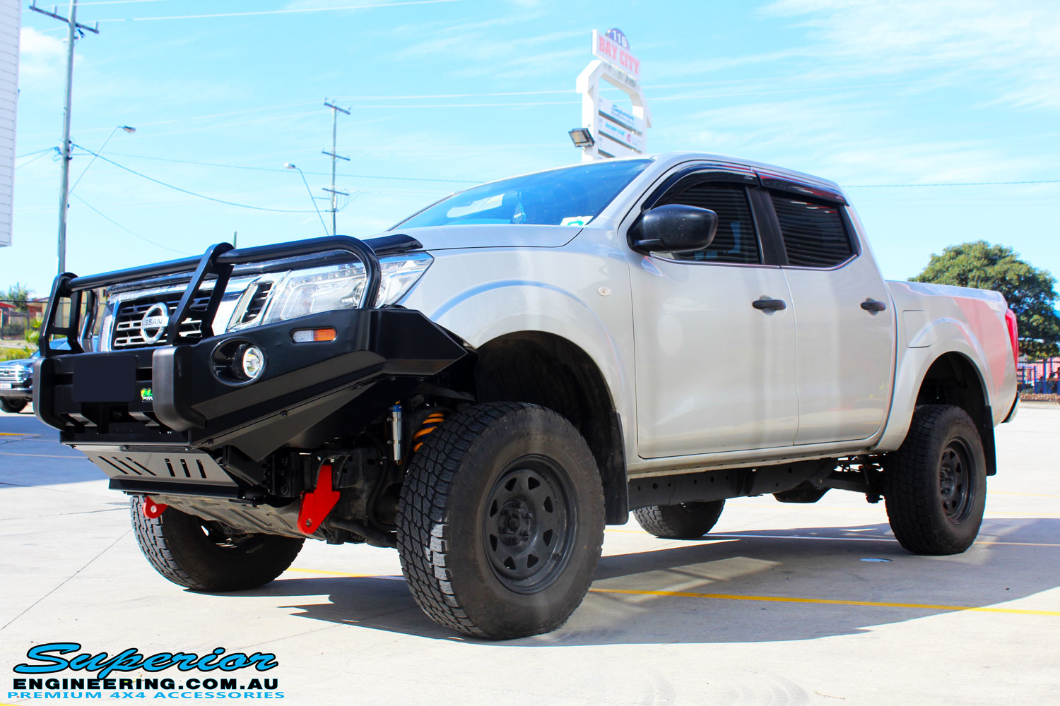 """Left front side view of a Grey Nissan NP300 Navara Ute after fitment of a Superior Remote Reservoir 2"""" Inch Lift Kit + Ironman 4x4 Deluxe Black Bull Bar & Superior 2"""" Inch Body Lift"""