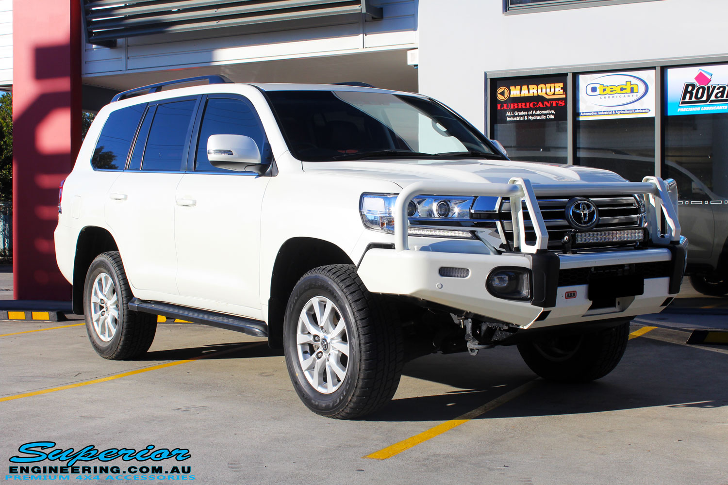 Right front side view of a Toyota 200 Series Cruiser Wagon in White being fitted with Superior Chromoly Upper Control Arms