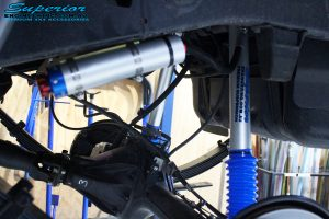 """Rear left close up underbody view of the fitted Superior 5"""" Inch Adjustable Remote Reservoir Shock and Mount + Leaf Spring"""
