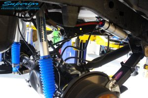 "Rear right underbody view of the fitted Superior 5"" Inch Adjustable Remote Reservoir Shocks and Mounts + Leaf Springs"