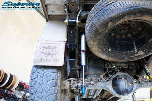 Left rear underbody shot of the fitted Piggy Back Remote Reservoir Shocks, U-Bolt Kit and Rear Leaf Springs