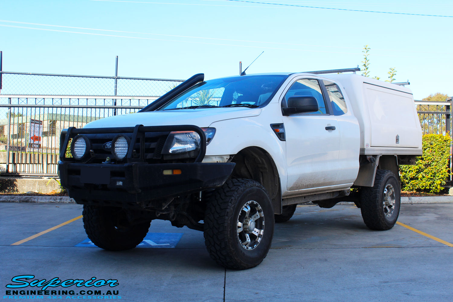 """Left front side view of a Ford PX Ranger in White after fitment of a Superior 2"""" Inch Remote Reservoir Lift Kit"""