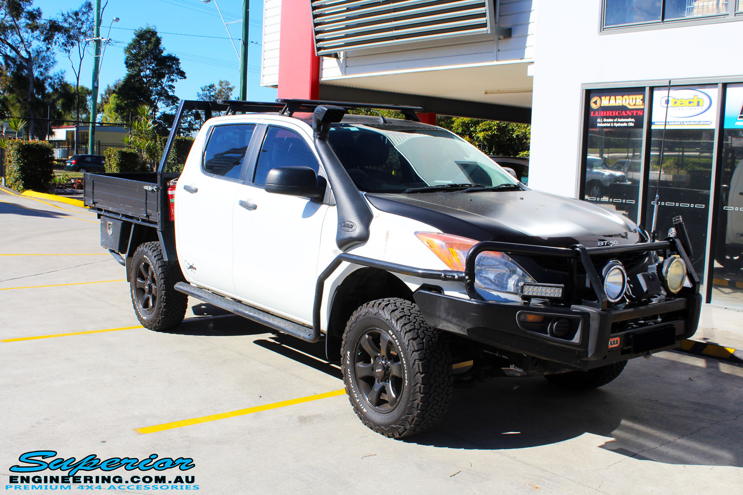 Right front side view of a Mazda BT-50 in White On The Hoist @ Superior Engineering Deception Bay Showroom