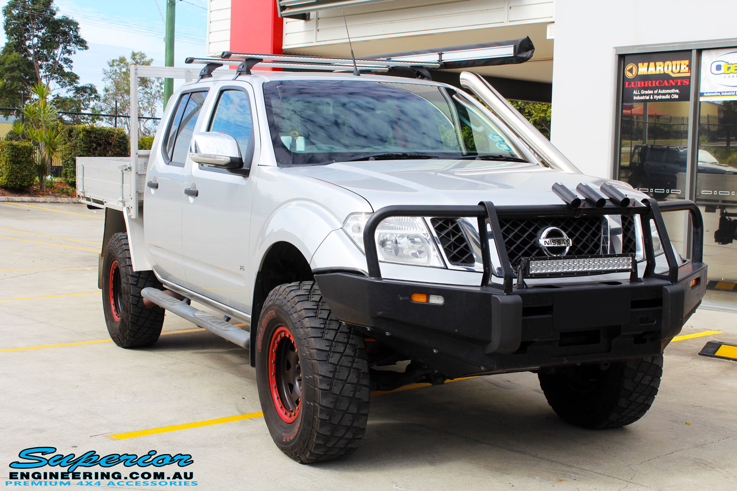 Right front side view of a Nissan D40 Navara in Silver On The Hoist @ Superior being fitted with a Chassis Brace/Repair Plate