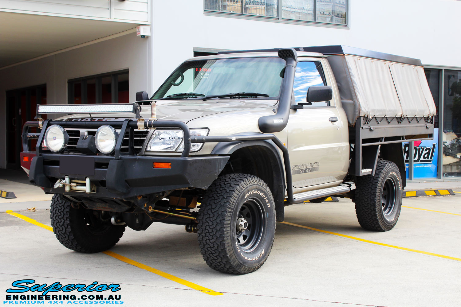 Left front side view of a Gold Nissan GU Patrol Ute being fitted with Superior Superflex Sway Bar Kit & a Superior Shock Tower Kit