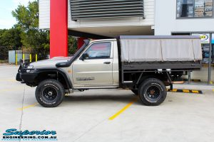 Left side view of a Gold Nissan GU Patrol Ute being fitted with Superior Superflex Sway Bar Kit & a Superior Shock Tower Kit