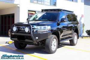 Left front side view of a Toyota 200 Series Landcruiser Wagon in Black after fitment of a Ironman 4x4 50mm Lift Kit with Superior Diff Drop Kit