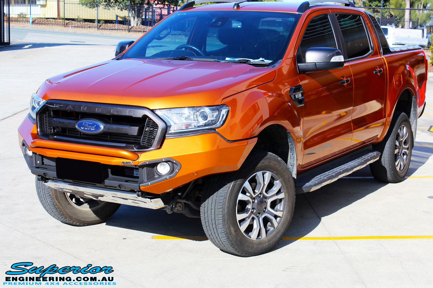 "Left front side view of a Orange Ford PXII Ranger Dual Cab after fitment with a Rhino 4x4 Evolution 3D Winch Bar & Legendex 409 Stainless Steel 3"" Inch Exhaust + Power Command Module"