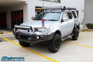 """Left front side view of a Mitsubishi MN Triton in Silver after fitment of a Superior Nitro Gas 2"""" Inch Lift Kit & Superior Chassis Repair Plate"""