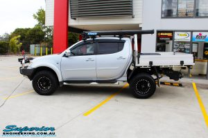 """Left side view of a Mitsubishi MN Triton in Silver after fitment of a Superior Nitro Gas 2"""" Inch Lift Kit & Superior Chassis Repair Plate"""