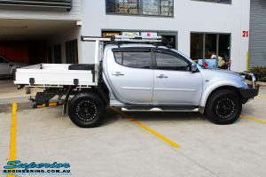 """Right side view of a Mitsubishi MN Triton in Silver before fitment of a Superior Nitro Gas 2"""" Inch Lift Kit & Superior Chassis Repair Plate"""