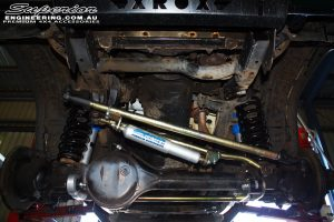 """Front underbody shot of the front fitted suspension components such as a Superior 4340m Heavy Duty Adjustable Drag Link, Superior Nitro Gas 2"""" Inch Shocks + Coil Springs, Front Heavy Duty Adjustable Panhard Rod, Superior 4340m Comp Spec Tie Rod & Superior Steering Damper"""