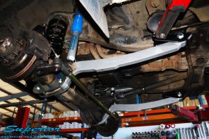 """Left underbody shot looking at the fitted Superior 3""""Inch Hybrid Superflex Arms, Superior Nitro Gas 2"""" Inch Shocks + Coil Springs & Superior 4340m Comp Spec Tie Rod"""