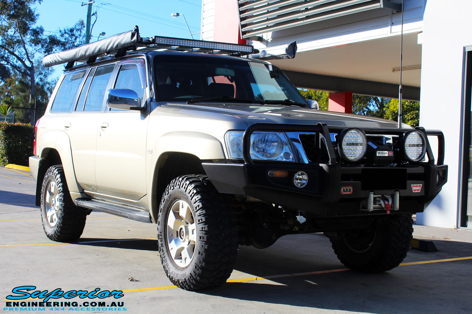 Right front side view of a Nissan GU Patrol Wagon in Gold On The Hoist @ Superior Engineering Deception Bay Showroom
