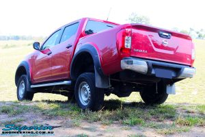 "Rear left side view of the Red Nissan NP300 Navara Dual Cab flexing after fitment of a Superior Remote Reservoir 3"" Inch Lift Kit"