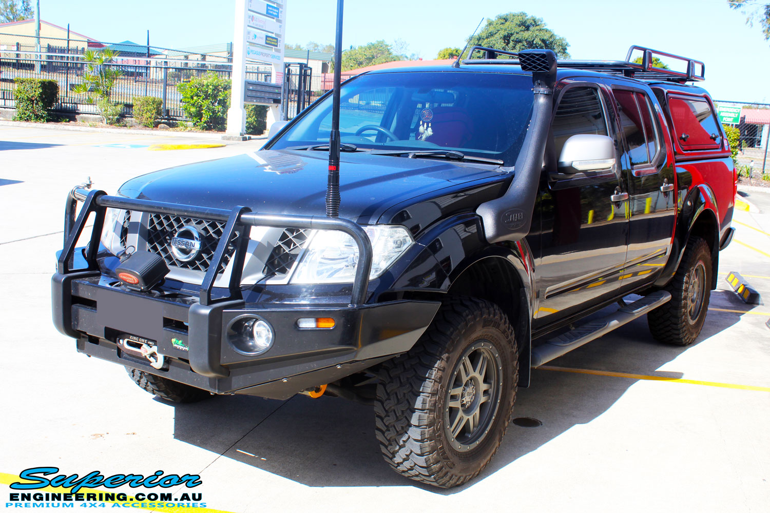 Right front side view of a Nissan D40 Navara in Black On The Hoist @ Superior being fitted with a Chassis Brace/Repair Plate