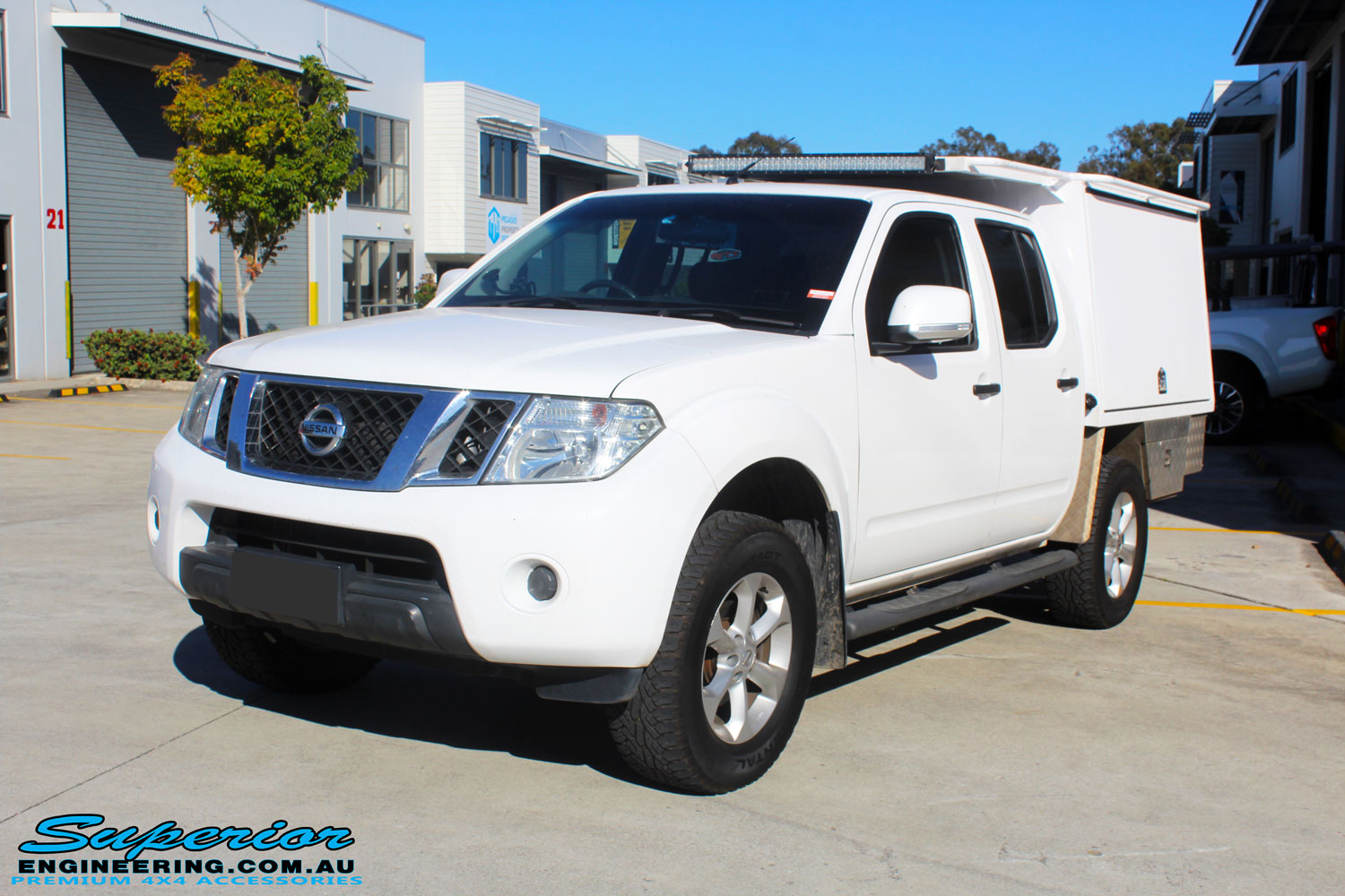 Left front side view of a Nissan D40 Navara in White On The Hoist @ Superior being fitted with a Chassis Brace/Repair Plate