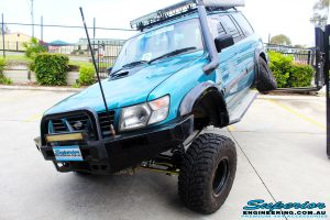 "Left front side view of a Blue Nissan GU Patrol flexing its left rear wheel after fitment of a Superior Nitro Gas Hyperflex 3"" Inch Lift Kit with Superior Control Arms Long Arm Kit"