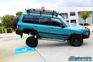 """Right side view of a Blue Nissan GU Patrol being flexed on its rear left wheel after fitment of a Superior Nitro Gas Hyperflex 3"""" Inch Lift Kit with Superior Control Arms Long Arm Kit"""