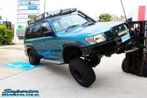 """Left front side view of a Blue Nissan GU Patrol being flexed on its front left wheel after fitment of a Superior Nitro Gas Hyperflex 3"""" Inch Lift Kit with Superior Control Arms Long Arm Kit"""