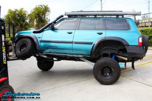 """Left side view of a Blue Nissan GU Patrol being flexed on its front left wheel after fitment of a Superior Nitro Gas Hyperflex 3"""" Inch Lift Kit with Superior Control Arms Long Arm Kit"""