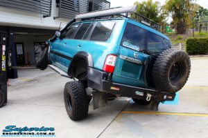 """Left rear side view of a Blue Nissan GU Patrol flexing on its front left wheel after fitment of a Superior Nitro Gas Hyperflex 3"""" Inch Lift Kit with Superior Control Arms Long Arm Kit"""