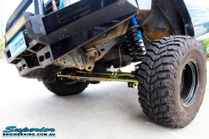 """Left front close up shot of the inside guard of a Blue Nissan GU Patrol being flexed on its rear left wheel after fitment of a Superior Nitro Gas Hyperflex 3"""" Inch Lift Kit with Superior Control Arms Long Arm Kit"""
