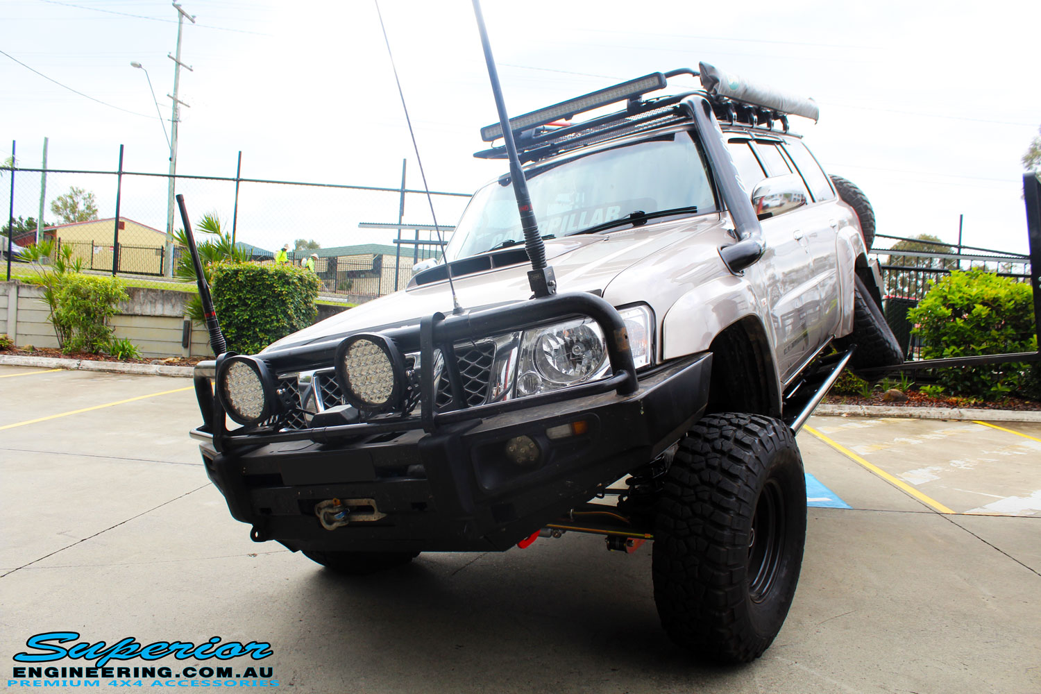 "Left front side view of a Gold Nissan GU Patrol showing its flex after fitment of a Superior Remote Reservoir Hyperflex 4"" Inch Lift Kit, Superior Control Arms Long Arm Kit, Superior Superflex Swaybar Front & Rear Kits, Superior 4340m Heim Joint Tie Rod with King Shocks"