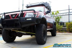 """Left side front view of a Red Nissan GU Patrol after fitment of a Superior Nitro Gas Hyperflex 5"""" Inch Lift Kit"""