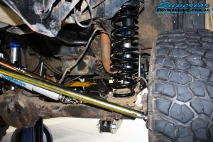Front left underbody shot looking at the fitted Superior Nitro Gas Shock with Coil Spring, Bumpstop Extension, Superior Hyperflex Radius Arms, Steering Damper, Drag Link Heim Joint 4340m Solid Bar and Adjustable Panhard Rod