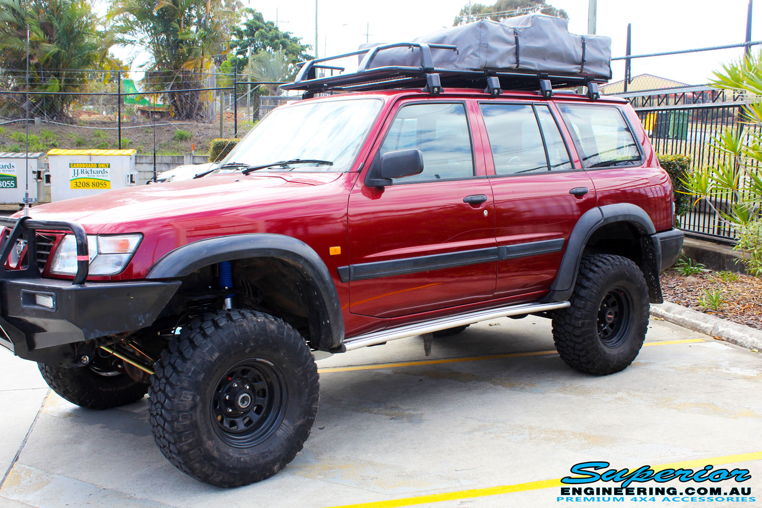 """Left side view of a Red Nissan GU Patrol after fitment of a Superior Nitro Gas Hyperflex 5"""" Inch Lift Kit"""